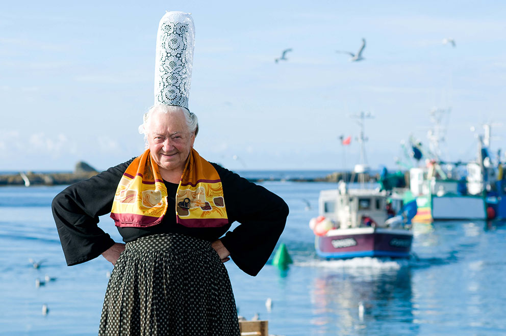 breton woman with headdress posing on a harbor in brittany on the seaside with fishing boats